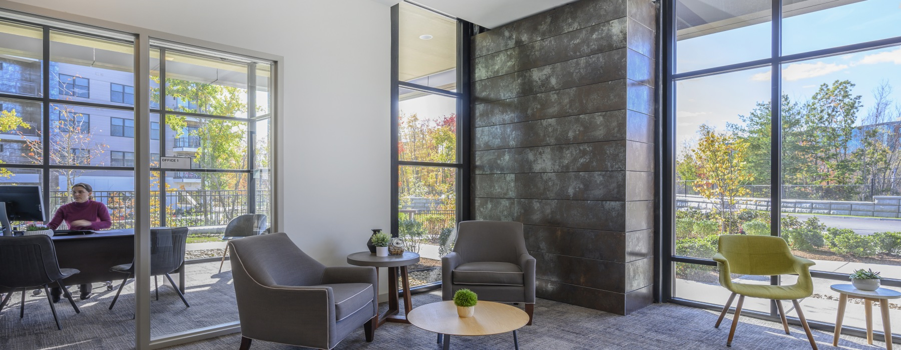 Sitting area and leasing office with leasing consultant sitting at her desk. Floor-to-ceiling windows with a view to the courtyard.