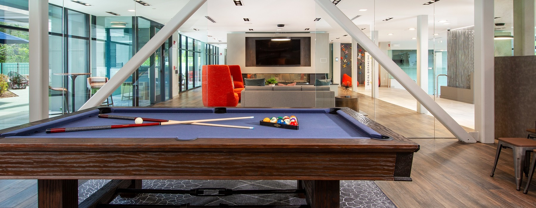 game room with pool table, lighting, flat screen TV and seating. View to outdoor seating area.
