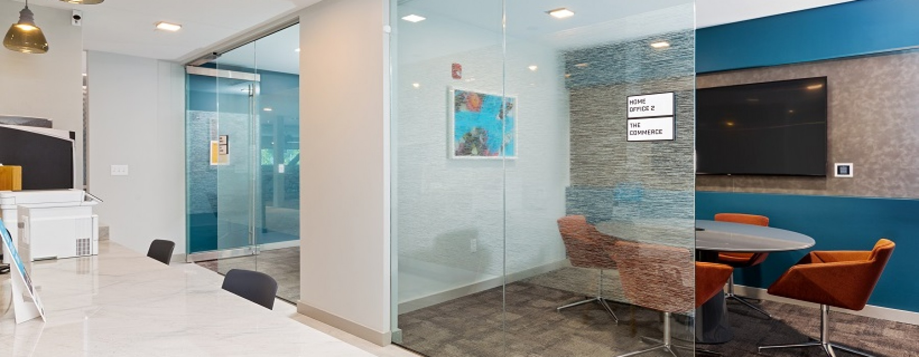 2 private work spaces with small table and flatscreen TV enclosed with glass. Open to printing station and coffee bar